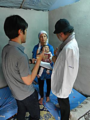 水頭症の子どもを診察する鎌田理事長